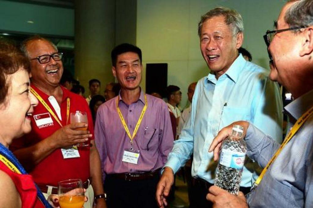 SOKONGAN DARI KELUARGA: Dr Ng (dua dari kanan) bergaul bersama juruterbang perintis pasukan Black Knights dan keluarga mereka di acara pranonton di Marina Barrage. - Foto MINDEF
