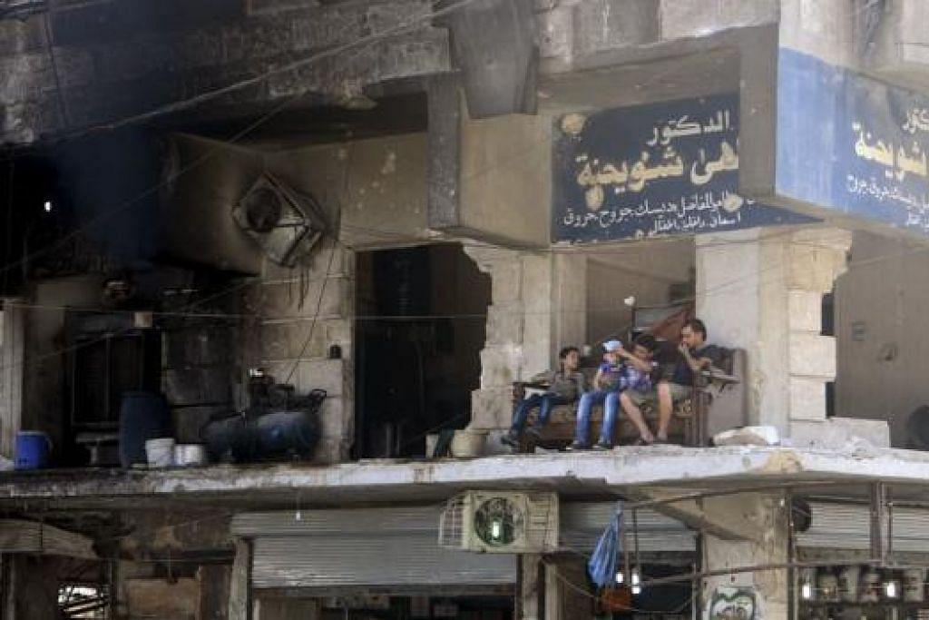 KEHIDUPAN DITERUSKAN: Di sebalik kemusnahan yang melanda, penduduk daerah al-Shaar di bandar Aleppo ini duduk bersantai di beranda sebuah bangunan yang mengalami kerosakan ekoran serangan. - Foto REUTERS