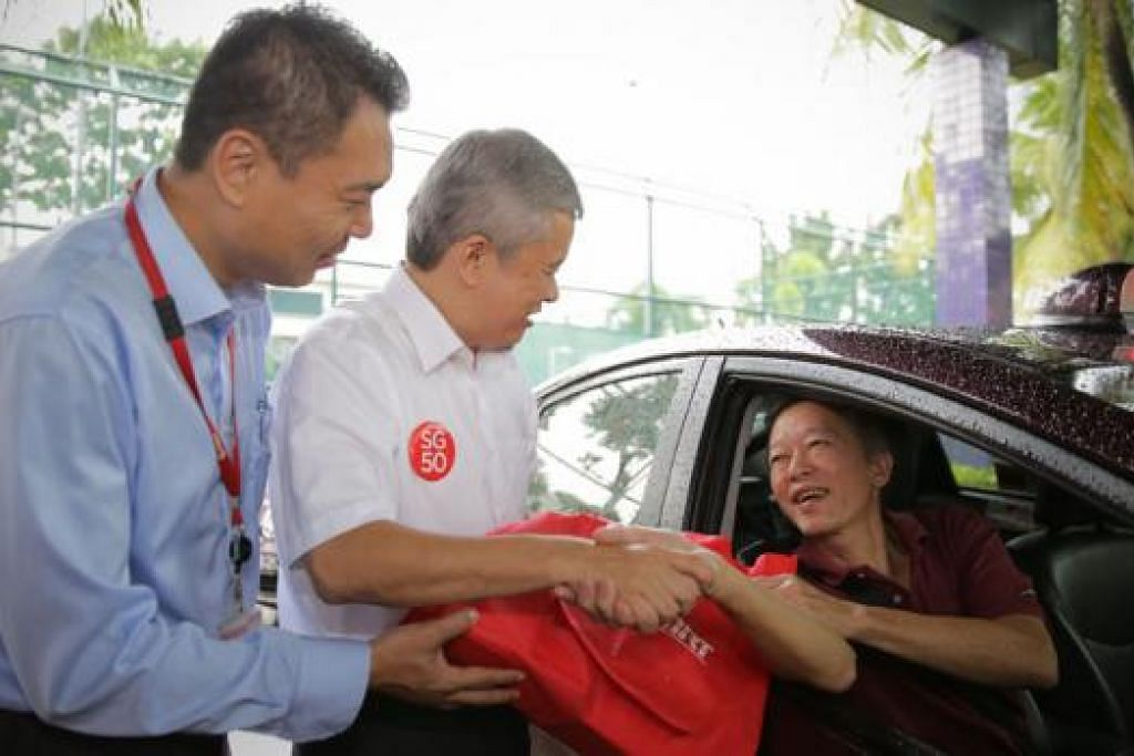 HABUAN UNTUK PEMANDU: Salah seorang pemandu teksi SMRT, Encik Lim Choon Seng, menerima beg hadiah SG50 daripada Encik Ang Hin Kee. - Foto THE STRAITS TIMES.
