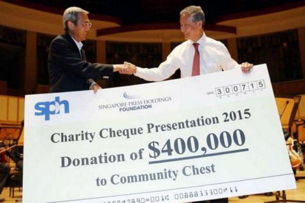 KONSERT PERCUMA: Dr Lee Boon Yang (kiri), menyerahkan cek bernilai $400,000 kepada Encik Eric Ang sebelum konsert SPH Gift Of Music yang ke-10 bermula di Dewan Konsert Esplanade, Khamis lalu. - Foto THE STRAITS TIMES