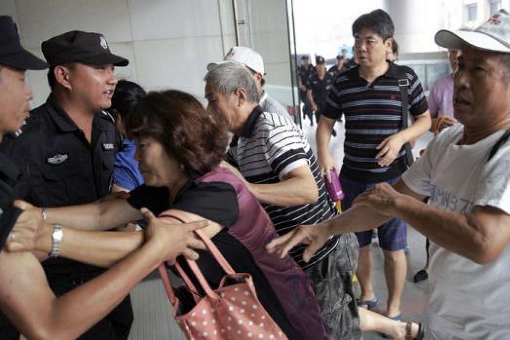 KECOH: Sanak saudara penumpang MH370 menolak anggota polis sedang mereka memasuki pejabat pesawat syarikat penerbangan MAS di Beijing. - Foto REUTERS