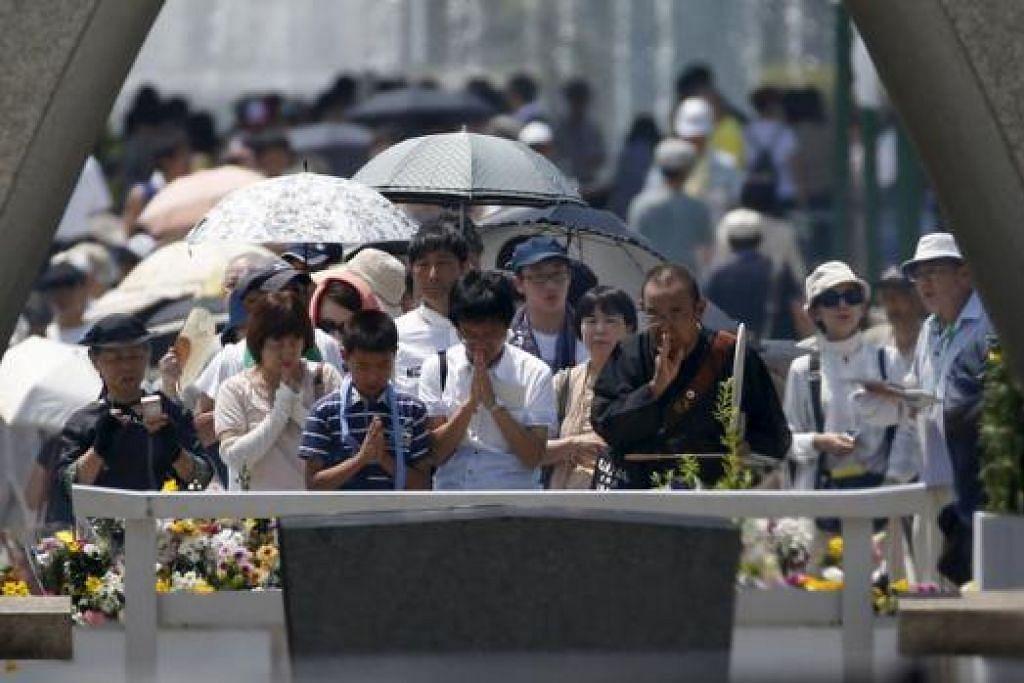 BERI PENGHORMATAN: Para pengunjung bertafakur di tugu di Hiroshima bagi memperingati mangsa pengeboman atom pada 1945. - Foto REUTERS