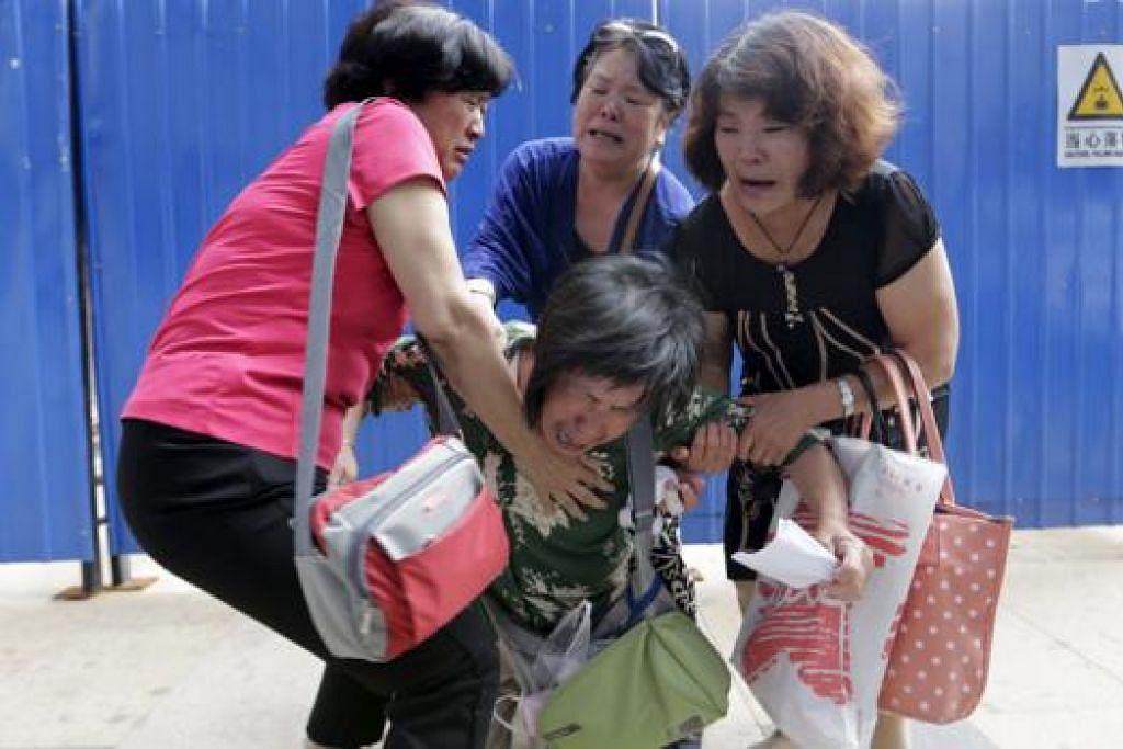 MERATAP: Cik Bao Lanfang (tengah) yang kehilangan anak lelaki, menantu perempuan dan cucu berusia tiga tahun dalam pesawat MH370 meratap di depan pejabat Malaysia Airlines di Beijing, China, semalam. - Foto REUTERS