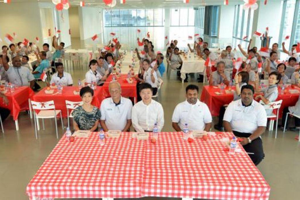 IKTIRAF SUMBANGAN PEKERJA: Encik Abdul Aziz (duduk meja depan, dua dari kanan) menjamu selera juadah nasi ayam bersama sebahagian 800 kakitangan pembersihannya kelmarin. - Foto M.O. SALLEH