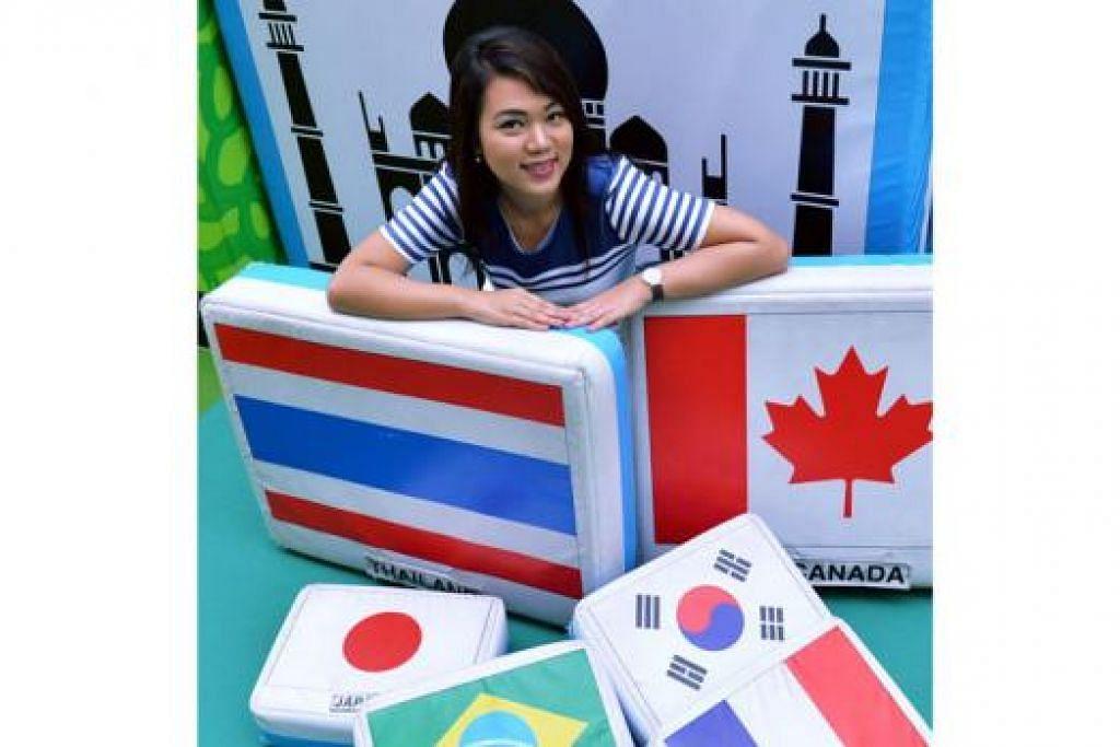 NOSTALGIA PERMAINAN LAMA: Pengurus pembangunan penonton dan kerjasama di Muzium Negara Singapura, Cik Farhana Raman, bersama seni pemasangan berupa pemadam raksasa dengan bendera yang popular sebagai permainan kanak-kanak dahulukala. - Foto-foto KHALID BABA