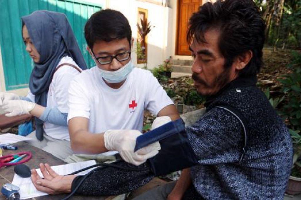 TURUN PADANG: Penulis, Encik Muhammad Nur Dinie (tengah), turut membantu menjalankan pemeriksaan kesihatan ke atas penduduk kampung di Sumatera.