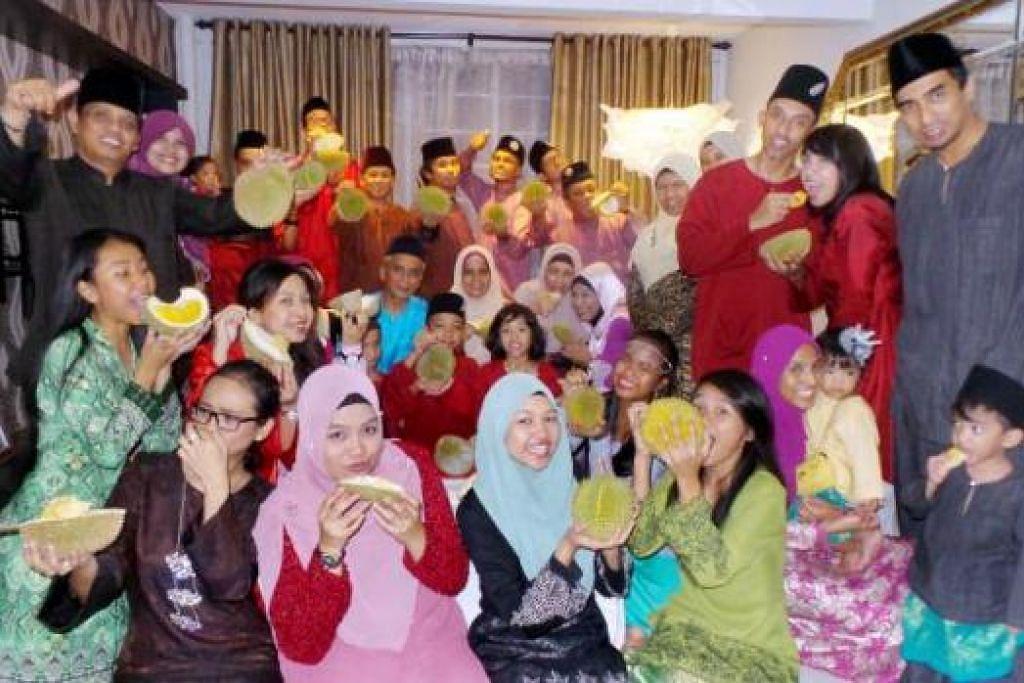PARTI DURIAN: Encik Jasri Bahari (berdiri, kanan, berbaju merah) berpendapat memang seronok kalau makan durian, yang juga merupakan raja segala buah di Singapura, beramai-ramai bersama ahli keluarga mentelah lagi negara ini menyambut ulang tahunnya yang ke-50 tahun ini. - Foto SHAHIDA SARHID