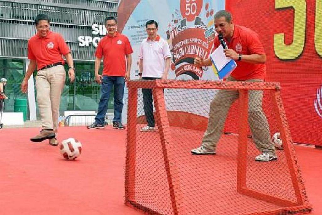 KARNIVAL SG50: Dr Maliki Osman (kiri) merasmikan pembukaan karnival dua hari di Hab Sukan Singapura dengan menendang bola, sempena sambutan ulang tahun Singapura ke-50 (SG50). - Foto KHALID BABA