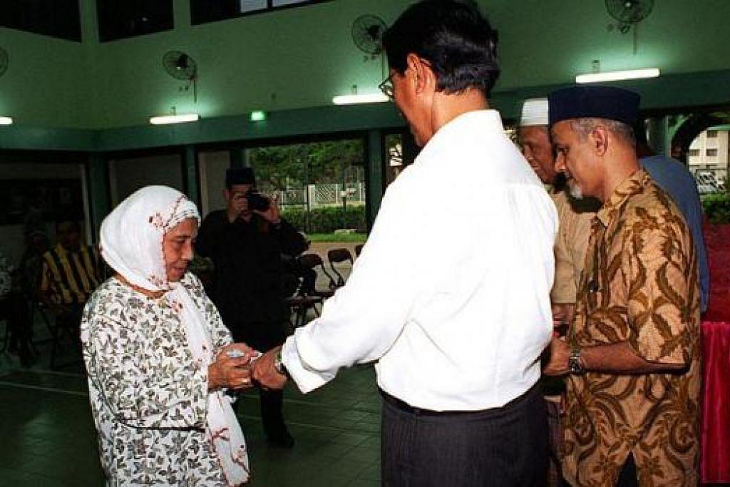 SAMPAIKAN SUMBANGAN HARI RAYA: Haji Sidek menyampaikan sumbangan Hari Raya kepada 48 penerima di Balai Rakyat Eunos pada 1998. – Foto fail