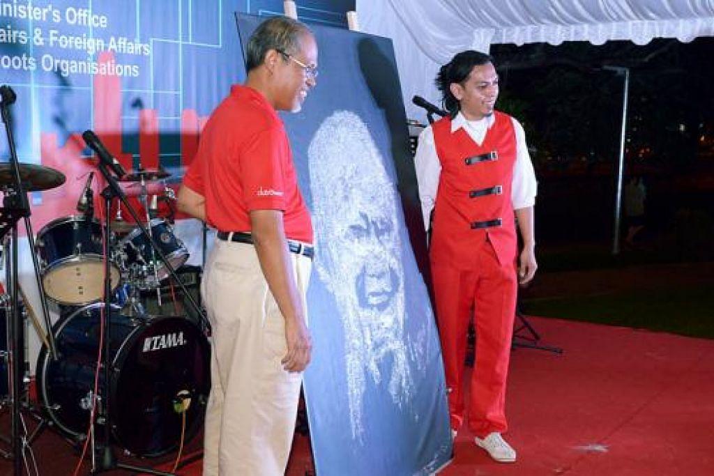 MENARIK DI KARNIVAL: Encik Imran Muhd Ishak (kanan) menyerahkan lukisan kilauan 'pop-art' yang menggambarkan potret mendiang Encik Lee Kuan Yew kepada Encik Masagos Zulkifli Masagos Mohamad. - Foto-foto TUKIMAN WARJI
