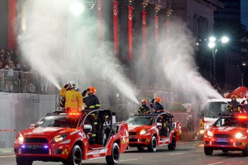 PERARAKAN KENDERAAN: (Gambar) Penonton tampak teruja dengan kenderaan 'Red Rhino' SCDF yang memancutkan air.