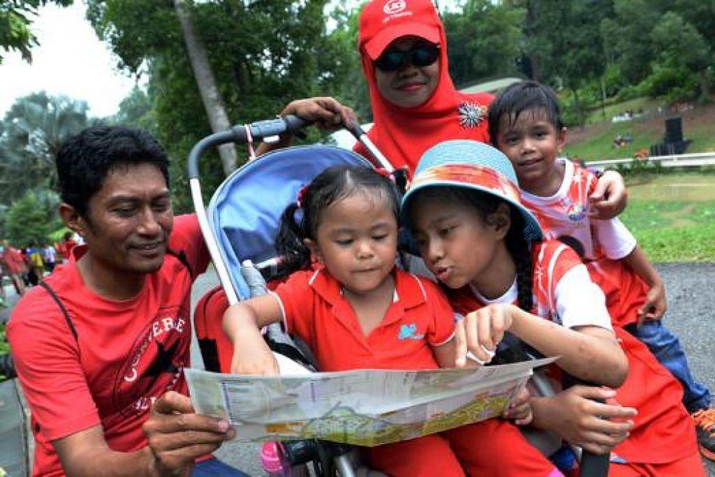 MERASAKAN PENGALAMAN FLORA DAN FAUNA: Dengan berpakaian serba merah, Encik Md Idros Idris, 45 tahun, isterinya, Cik Norhayati, dan anak mereka - Halimatus Saadiah, lapan tahun (tengah), Noor Ali, lima tahun (kanan), dan Nur Ain Emilia, tiga tahun, menyambut cuti Hari Kebangsaan dengan mengunjungi Kebun Bunga Singapura. - Foto TAUFIK A. KADER