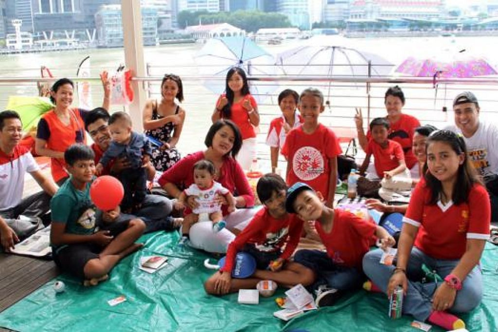 DATANG AWAL: Lebihi 20 orang keluarga Cik Shwiyah Mokhthiri (di barisan belakang lima dari kiri), datang 'berkelah' di kawasan gedung Marina Bay Sands seawal 9 pagi untuk meraikan Hari Kebangsaan. - Foto ANISA ABDULLAH