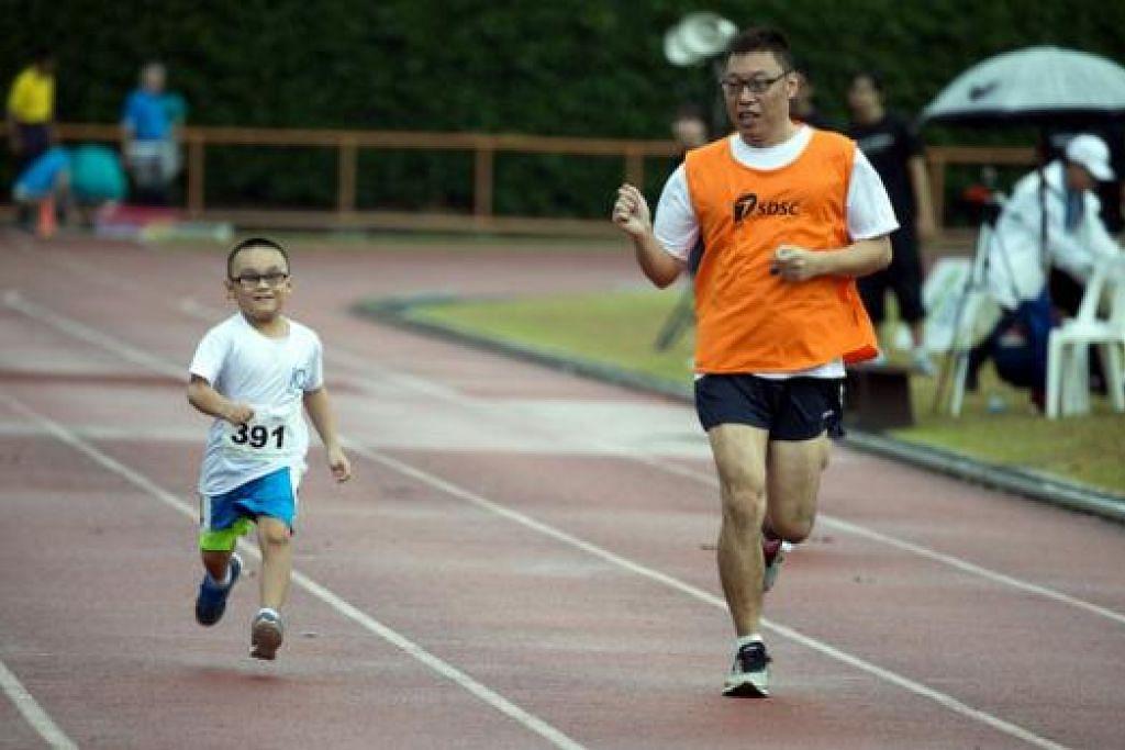 LARIAN SI CILIK: Atlit muda yang mengalami masalah penglihatan, Tony Wang, daripada iC2 PrepHouse, memecut laju dengan bantuan 'pemandunya' (kanan) yang berlari di sebelahnya. – Foto LAWRENCE LOH