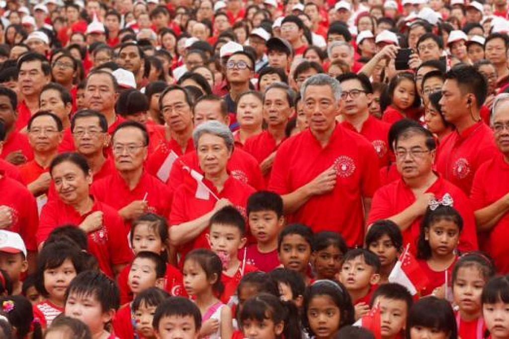 MELAFAZKAN IKRAR NEGARA: Encik Lee Hsien Loong (tiga dari kanan) dan isterinya Cik Ho Ching (empat dari kanan), semalam menghadiri majlis memperingati Hari Kebangsaan di Ango Mo Kio semalam. - Foto THE STRAITS TIMES