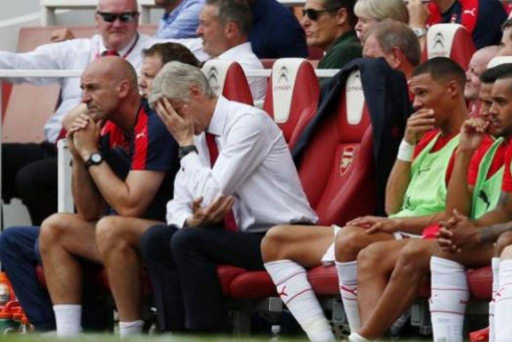 WAJAH KECEWA: Pengurus Arsenal, Arsene Wenger (menutup muka), seperti tidak percaya dengan prestasi hambar pasukannya semasa kekalahan kepada West Ham kelmarin. - Foto REUTERS