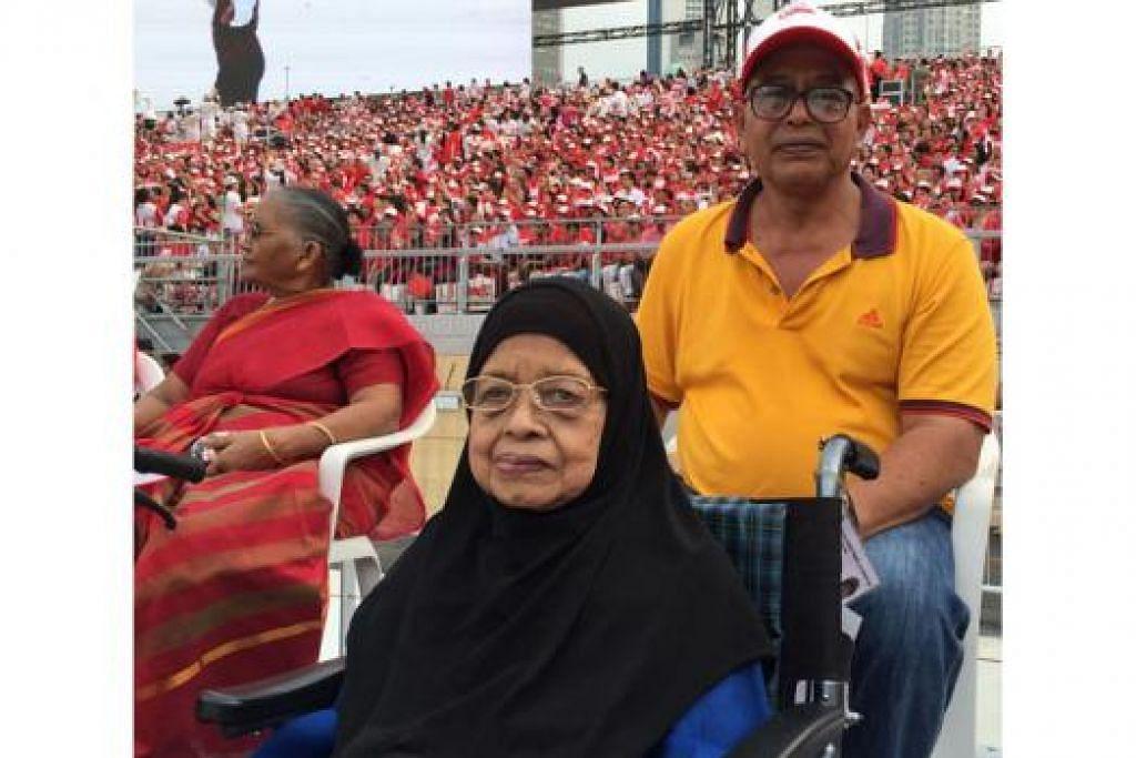 TIDAK MAHU KETINGGALAN: Walaupun terpaksa menggunakan kerusi roda untuk bergerak, Hajah Esah Moin, 82 tahun, tetap ghairah dan gembira dapat menyambut ulang tahun ke-50 Singapura. Beliau ditemani anaknya, Encik Ahmadshah Amir.