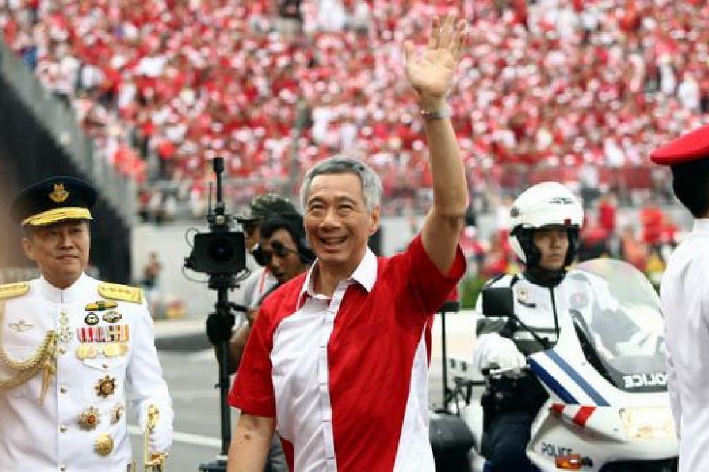 LAMBAIAN HARI BERSEJARAH: Perdana Menteri, Encik Lee Hsien Loong, melambai ke arah ribuan penonton yang membanjiri Padang untuk meraikan sambutan jubi emas Singapura yang diraikan penuh meriah dan gemilang kelmarin. - Foto ZAOBAO