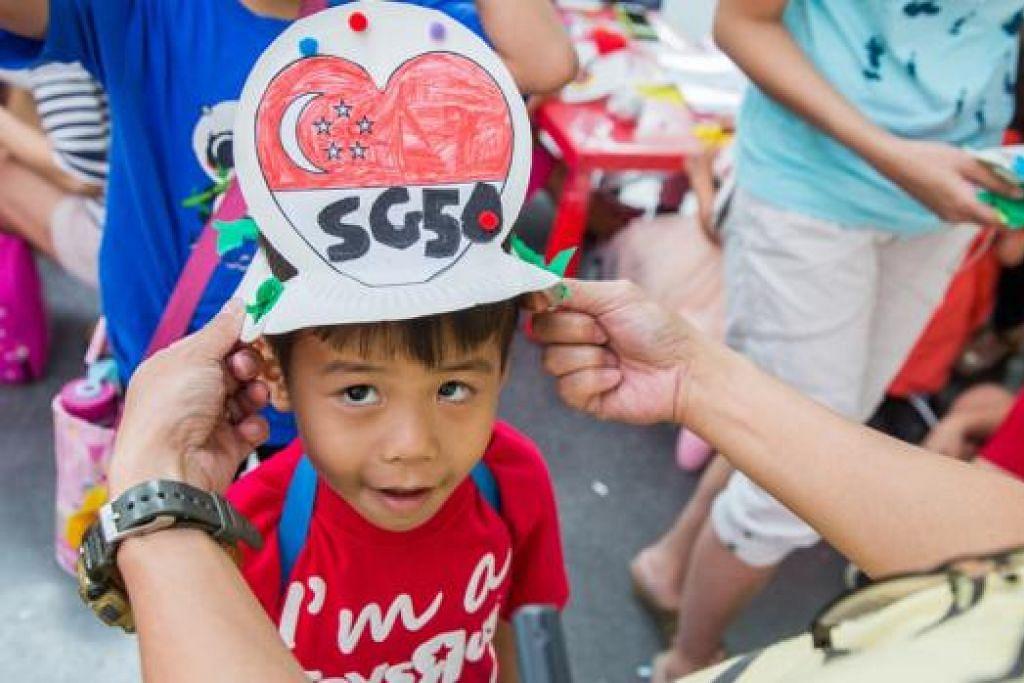 TOPI REKAAN SG50: Seorang warga cilik gembira dapat memakai topi rekaan SG50 yang dibuat di acara Masak Masak 2015 di Muzium Negara Singapura. - Foto MUZIUM NEGARA SINGAPURA