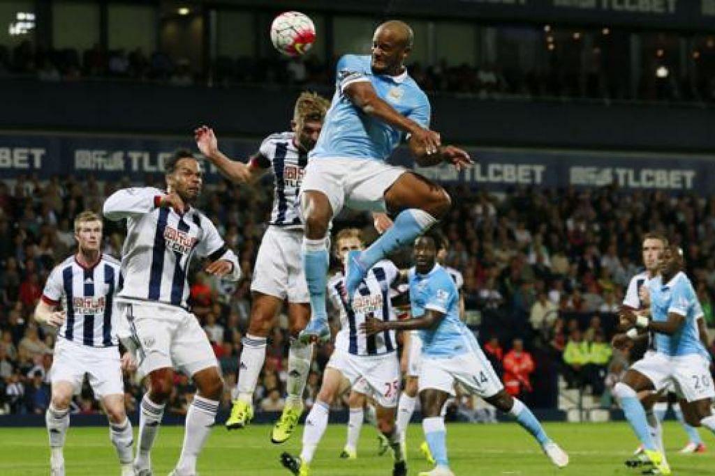 PASTIKAN KEMENANGAN: Kapten Vincent Kompany (jersi biru) melompat tinggi menanduk masuk gol ketiga Manchester City ketika menumpaskan West Bromwich Albion 3-0 di Stadium The Hawthorns awal pagi semalam. - Foto REUTERS