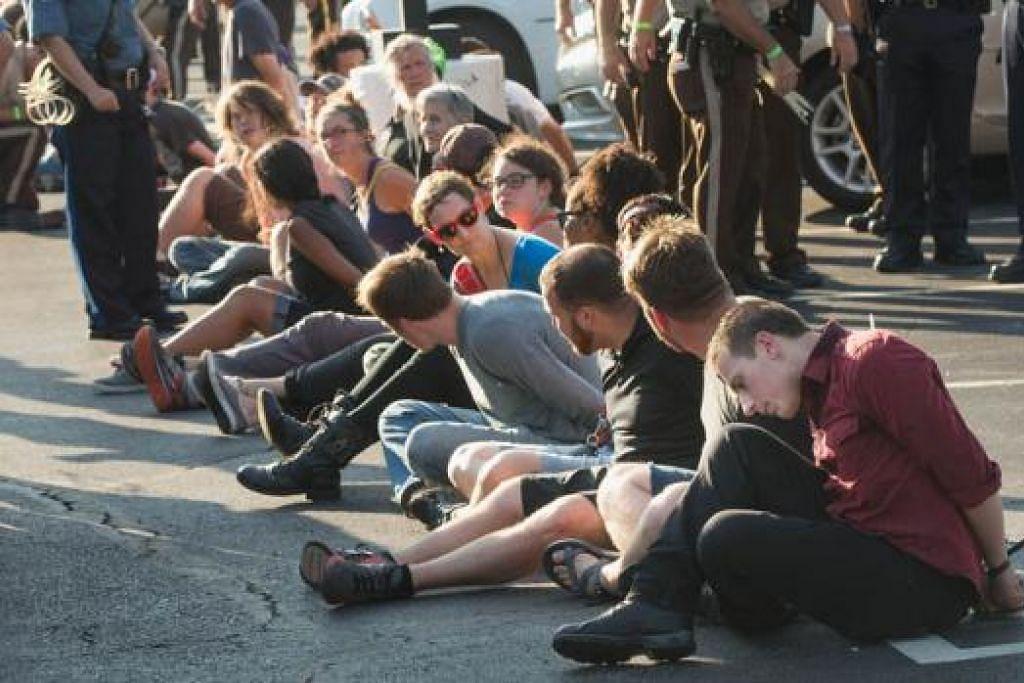 DITANGKAP: Lebih 60 orang yang menyertai tunjuk perasaan sebagai mengingati ulang tahun pertama kematian remaja ditembak polis berkulit putih ditahan polis Missouri kelmarin. - Foto AFP