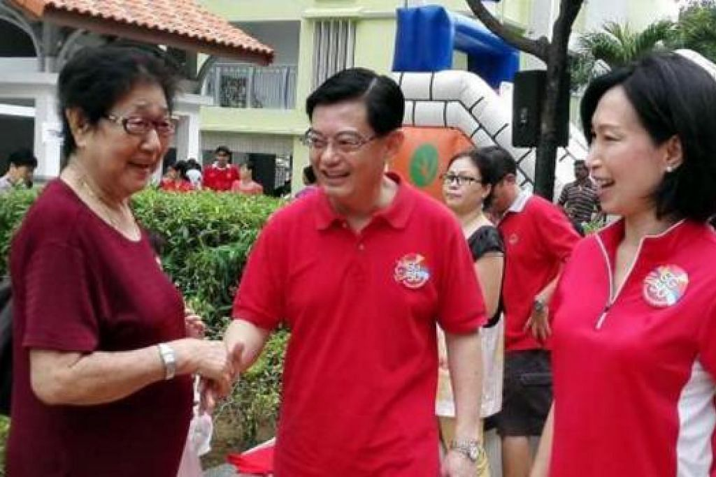 BERUNDUR DARIPADA POLITIK: Cik Irene Ng (kanan) dan Encik Heng Swee Keat (tengah) bertemu dengan penduduk semasa Karnival Keluarga Hari Kebangsaan di Tampines Changkat semalam. - Foto ST