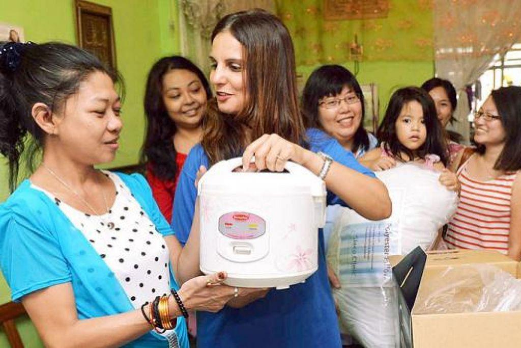 BERSYUKUR: Cik Sarah Abdul Hassan (kiri) bersyukur menerima barangan rumah daripada Ketua Bakat dan Pegawai Khidmat Pelanggan bagi Courts Asia Limited, Cik Kiran Kaur. - Foto KHALID BABA