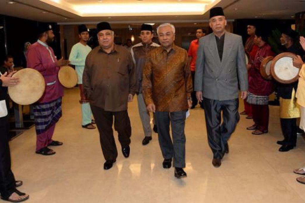 SANJUNGAN BUAT PEMIMPIN: Encik Hawazi Daipi (tengah berbaju batik) diapit Ustaz Ali (di kanannya) dan Setiausaha Masjid Khadijah, Encik Abdul Rahim Kassim, di majlis makan malam amal yang turut menjunjung budi beliau. - Foto TAUFIK A. KADER