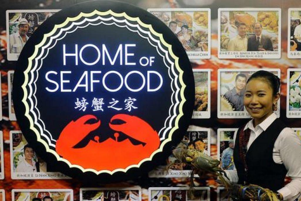 TARIK PELANGGAN: Pengurus Home of Seafood, Cik Nur Emiliana Abdul Rahman, bersama beberapa ketam liar yang bakal dimasak. Di belakangnya ialah gambar antara tetamu VIP yang pernah berkunjung ke restoran ini.