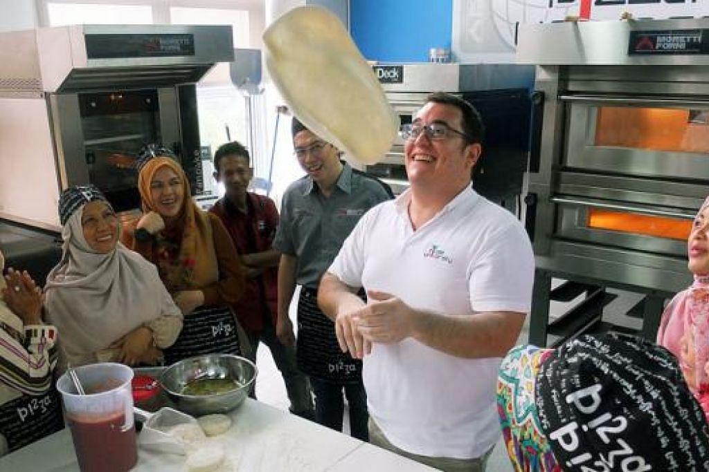 HARGAI INTERAKSI BERBILANG KAUM: Jurulatih Pizza University dari Italy, Encik Francesco Crispo (sedang melambung tepung piza), dan jurulatih dari Jakarta, Encik Dicky Tjitra (kelima dari kiri), seronok menyebar ilmu piza kepada kaum ibu daripada Jabatan Muslimah, Masjid Taklim Jabal Arafah di Nagoya Hill, Batam.