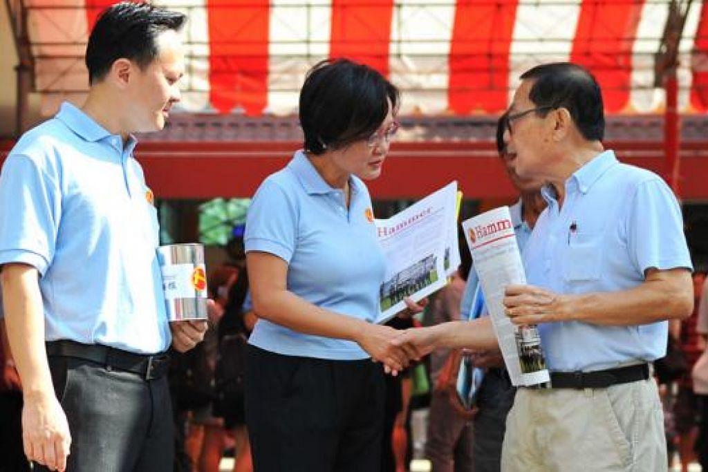 TEMUI PENDUDUK: Pengerusi WP Cik Sylvia Lim (tengah) menemui seorang penduduk semasa mengadakan lawatan ke pusat penjaja makanan Chong Pang. - Foto THE STRAITS TIMES