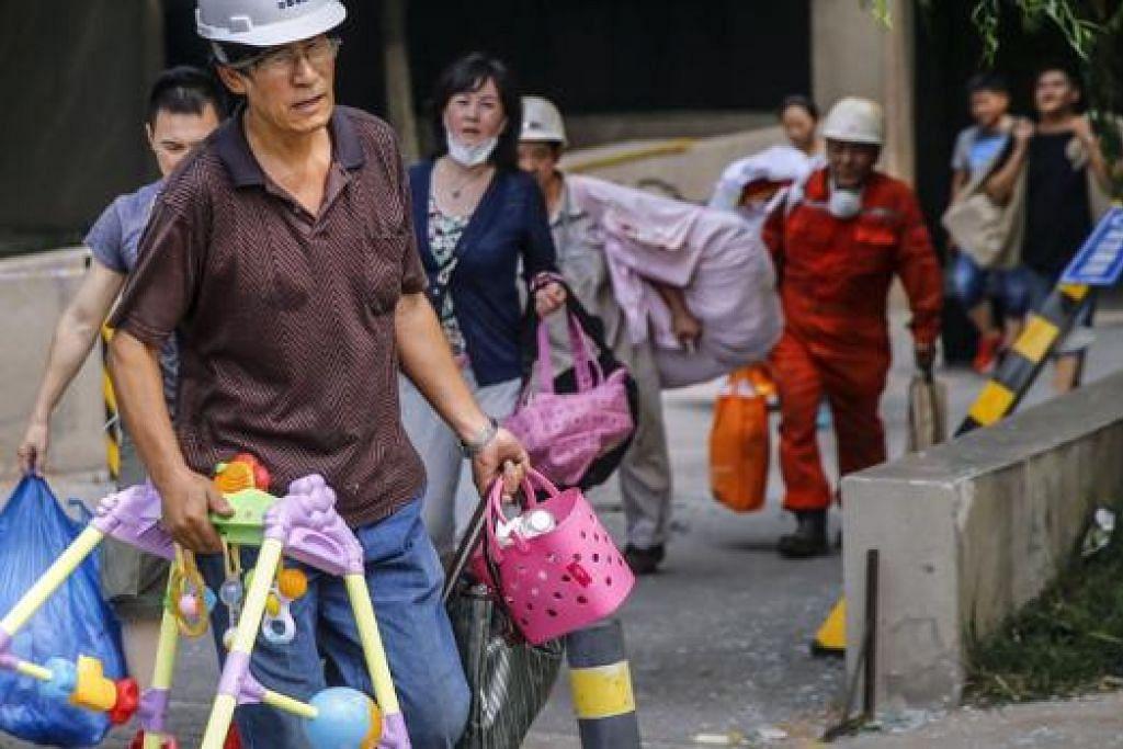BERPINDAH: Penduduk yang tinggal berhampiran kawasan letupan di Tianjin terpaksa meninggalkan kediaman masing-masing. - Foto AFP