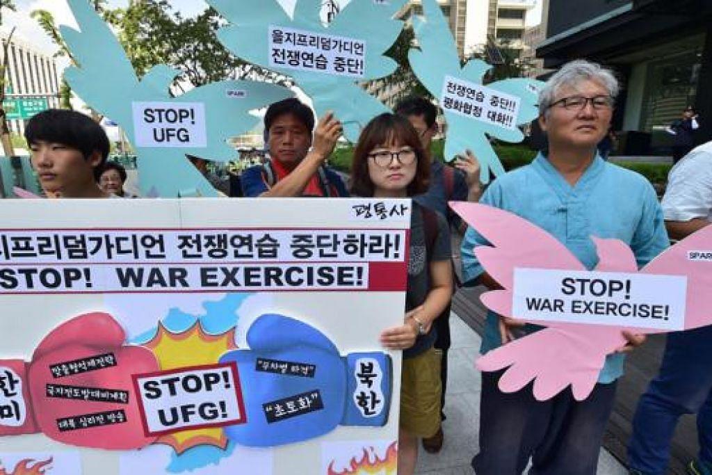 HENTIKAN LATIHAN TENTERA: Aktivis antiperang Korea Selatan mengadakan bantahan sewaktu perhimpunan bagi mengutuk latihan ketenteraan Amerika Syarikat-Korea Selatan yang bermula semalam. - Foto AFP