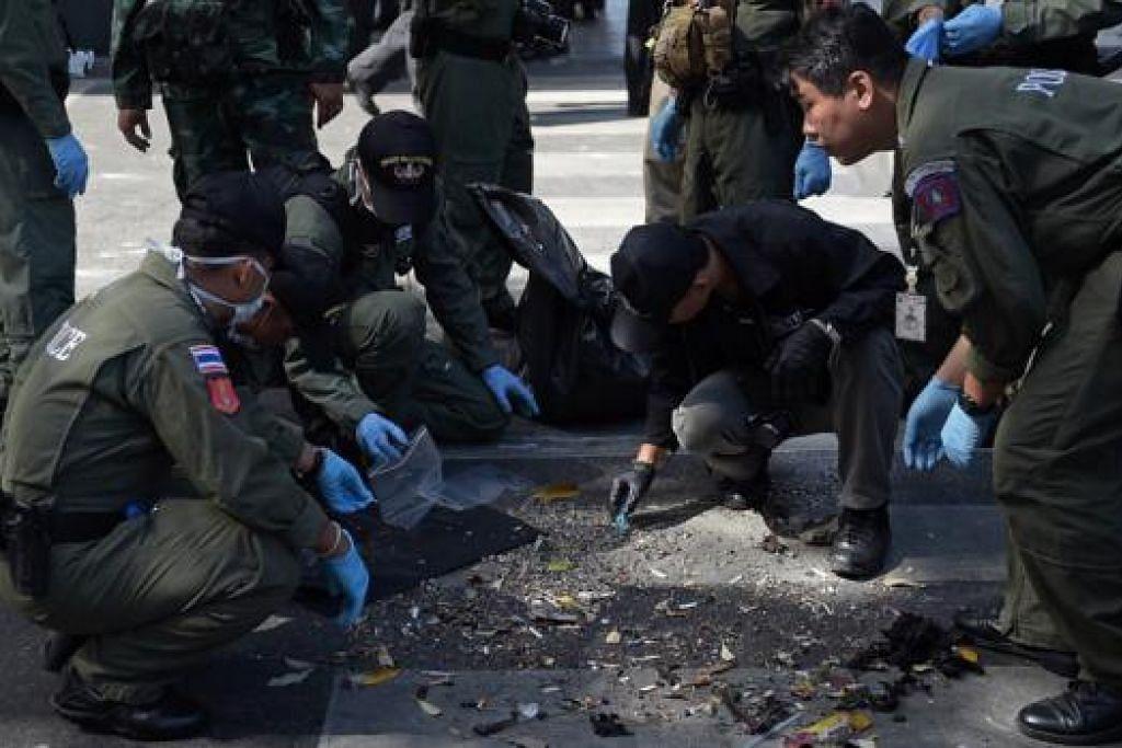 CARI BUKTI: Polis Thailand semalam mengepung kawasan letupan bagi menyaring puing-puing letupan dalam usaha mencari bukti dalang serangan bom tersebut semalam. - Foto AFP