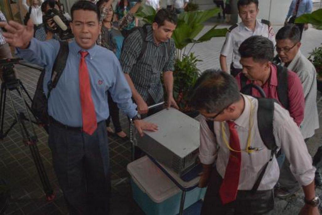 Pegawai polis merampas peralatan dari pejabat 1MDB di Kuala Lumpur pada 8 Julai lalu. Beberapa anggota pasukan petugas khas pemerintah yang sedang menyiasat syarikat itu telah ditahan berhubung dakwaan ada kebocoran dalam siasatan itu. Gambar AFP.