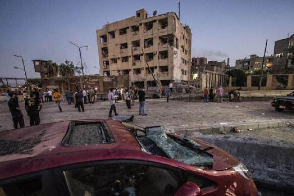 KESAN LETUPAN: Sebuah kereta dan bangunan keselamatan Mesir mengalami kerosakan teruk berikutan serangan bom kereta. Sebuah kumpulan militan yang menyokong militan Negara Islam (IS) mendakwa melakukannya. - Foto AFP