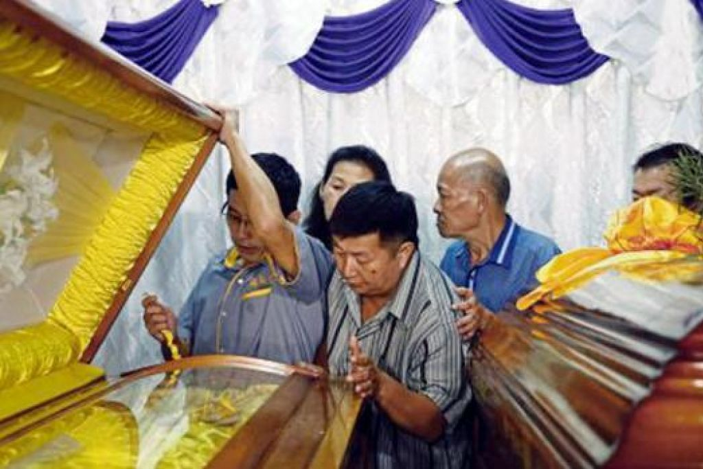 MENAHAN SEBAK: Encik Neoh Hock Guan (tengah) menatap keranda isteri dan anaknya yang maut dalam letupan bom di Bangkok di rumah mereka di Butterworth, Malaysia. - Foto REUTERS