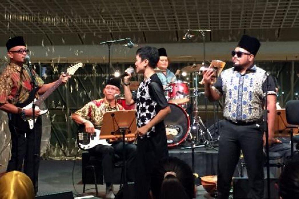 TENAGA ADIK-BERADIK: Empat daripada lima anak Salim I, (dari kiri) Jamal Salim, Zainudin Salim (duduk), Zubaidah Salim dan Rudi Salim, berada di atas pentas bersama kugiran band Wisma II bagi mendendangkan lagu 'O Salamah' pada malam persembahan 'Pujaan Hatiku - Salim I Tribute' yang diadakan sempena Pesta Raya 2015 pada 13 Ogos lalu di Esplanade Concourse. - Foto-foto NURMAYA ALIAS