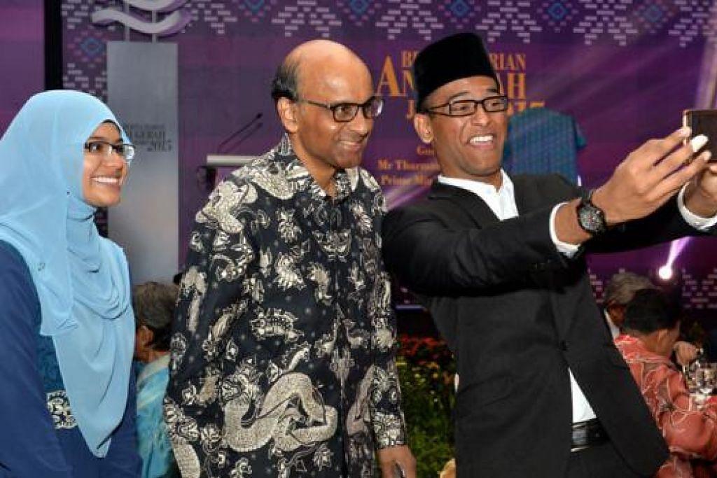 GAMBAR BUAT KENANGAN INDAH: Penerima Anugerah Jauhari Harapan, Encik Ahmad Abdurrahman Hanifah Marican (kanan) dan Cik Amalina Ridzuan, kelihatan sungguh gembira dapat bergambar dengan Timbalan Perdana Menteri Tharman Shanmugaratnam.