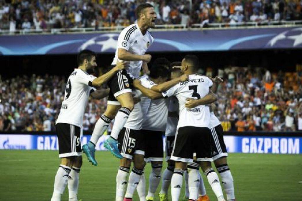 RAIKAN KEMENANGAN: Para pemain Valencia meraikan kemenangan 3-1 ke atas Monaco yang mencerahkan laluan mereka ke Liga Juara-Juara. - Foto AFP