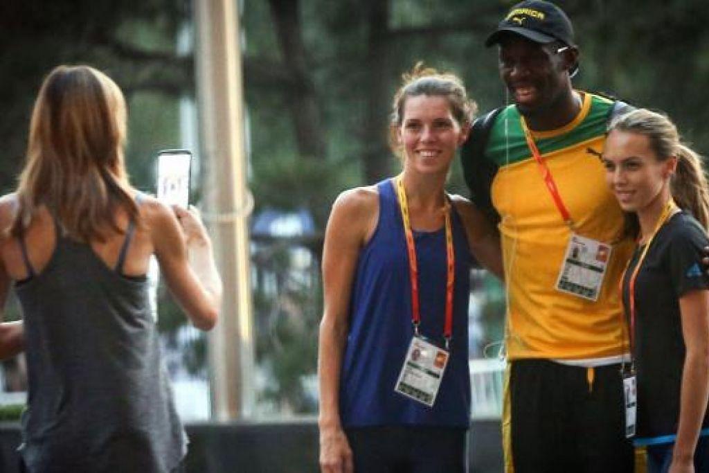 LAYAN PEMINAT: Usain Bolt bergambar dengan peminatnya menjelang beraksi di Kejohanan Dunia hari ini. - Foto AFP