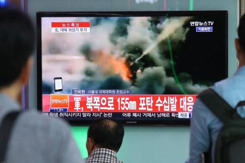 SERANG BALAS: Orang ramai menonton laporan berita mengenai serangan roket Korea Selatan di Seoul kelmarin. – Foto AFP