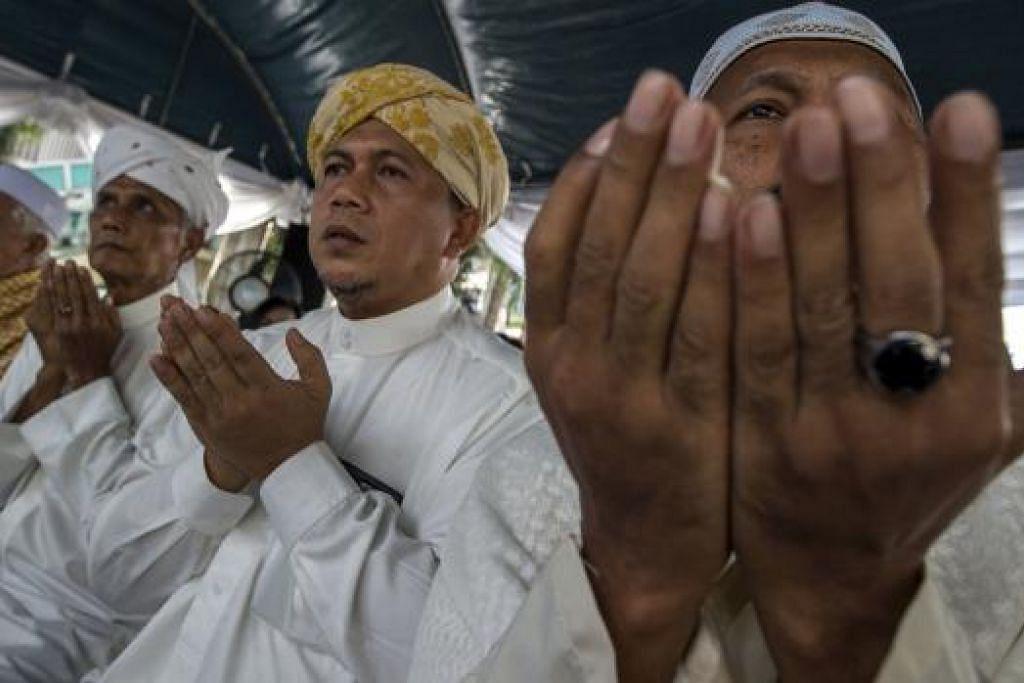 BERDOA MOHON KEAMANAN: Warga Muslim Thailand mengadakan upacara berdoa beramai-ramai memohon agar Bangkok diselamatkan daripada bencana, berhampiran dengan Kuil Erawan semalam. - Foto REUTERS