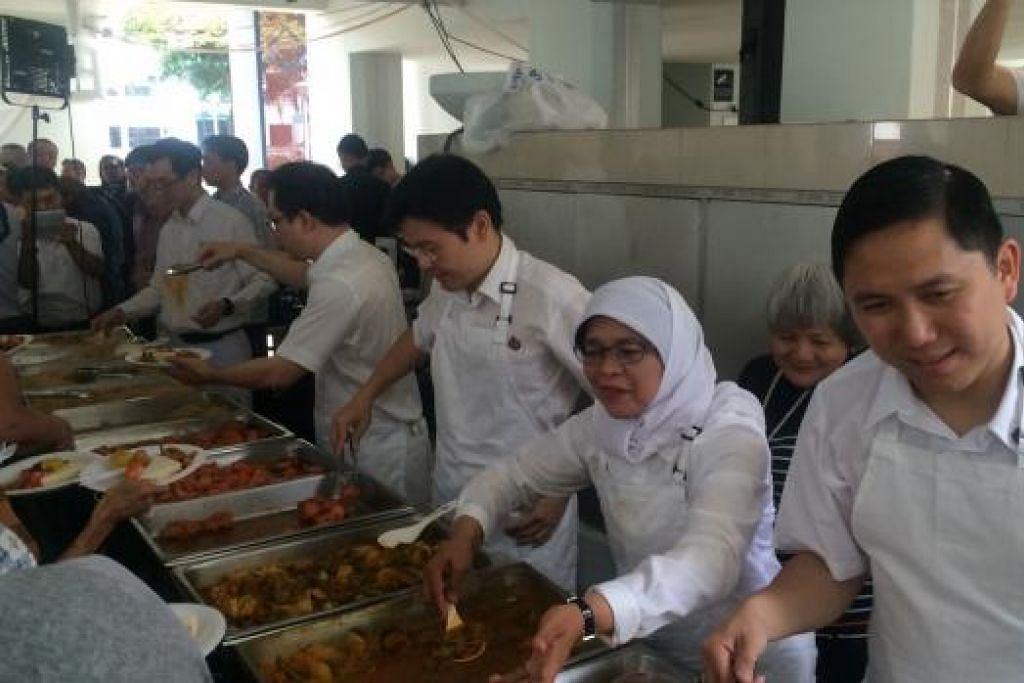Calon-calon PAP GRC Marsiling-Yew Tee sedang menyajikan makanan tengah  hari kepada sekitar 300 penduduk rumah sewa di Marsiling Blok 3 dan 4 dalam satu acara kemasyarakatan tadi. (Dari kanan) Encik Alex Yam, Cik Halimah Yacob, Encik Lawrence Wong dan Encik Ong Teng Koon. Gambar oleh Farid Hamzah