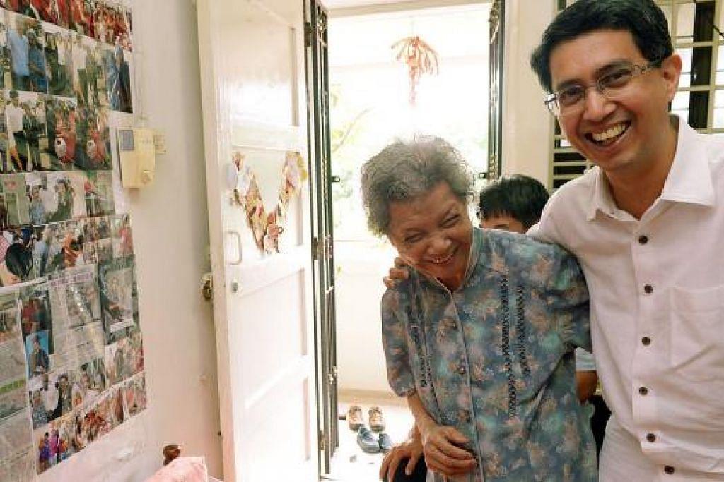 MESRA: Cik Su Ye Chu, 88 tahun, gembira menerima kunjungan Dr Faishal ke flatnya di Yishun. Kelihatan di tembok rumahnya gambar-gambar Dr Faishal yang dikagumi Cik Su. - Foto TUKIMAN WARJI