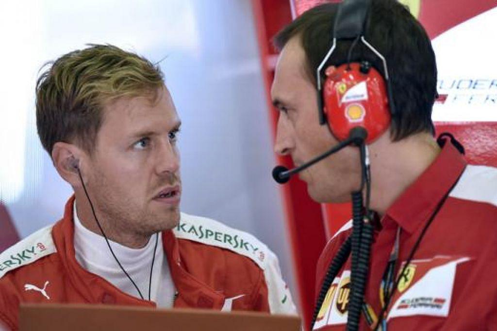MARAHKAN PEMBEKAL TAYAR: Pemandu Ferrari, Sebastian Vettel (kiri), berbincang dengan seorang pegawai teknikal pasukannya. selepas tayar kereta yang dipandunya meletup, meragut peluangnya menaiki podium di GP Belgium kelmarin. - Foto-foto AFP