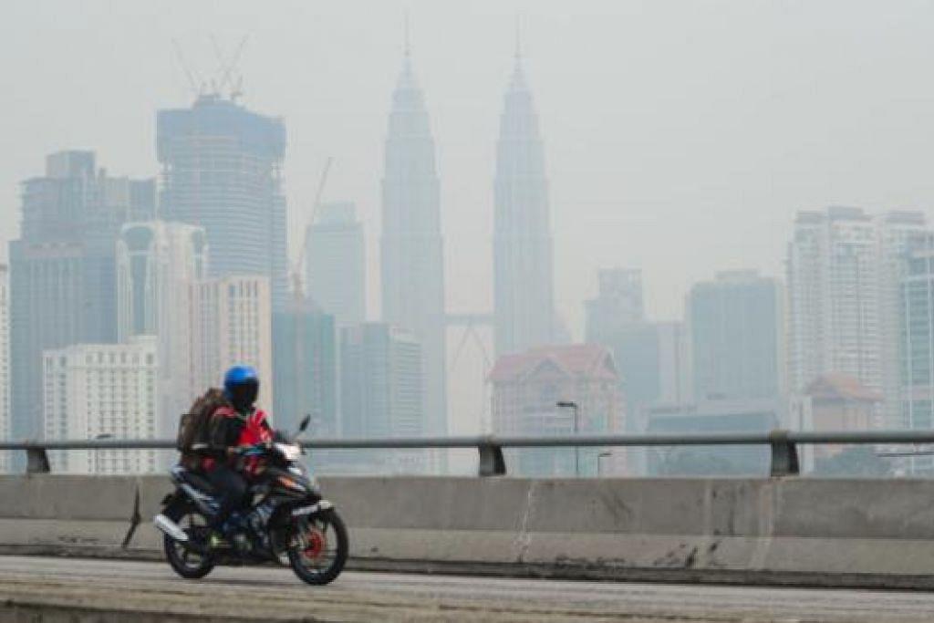 Mercu tanda Malaysia, Menara Kembar Petronas, kelihatan samar-samar akibat jerebu di Kuala Lumpur Isnin lalu. Empat bahagian di Sarawak juga diselubungi jerebu, mengakibatkan mutu udara merosot ke paras tidak sihat. Gambar AFP