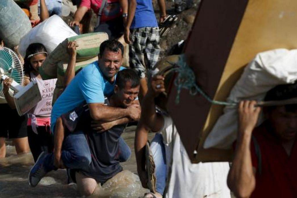 PULANG KE TANAH AIR: Krisis di sempadan antara Colombia dengan Venezuela menyebabkan beratus-ratus warga Colombia meninggalkan Venezuela bersama harta benda mereka bagi mengelakkan dihantar pulang. - Foto REUTERS