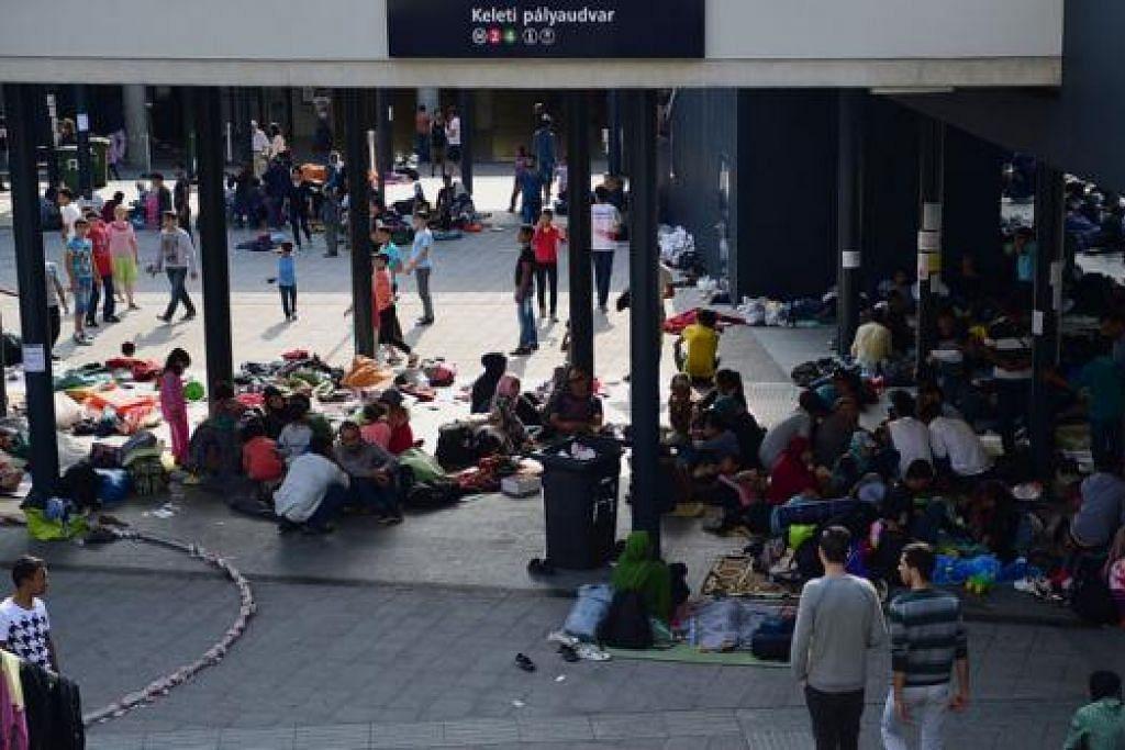 CARI PERLINDUNGAN: Pelarian dari beberapa negara mencari perlindungan di stesen-stesen kereta api di Budapest. - Foto AFP