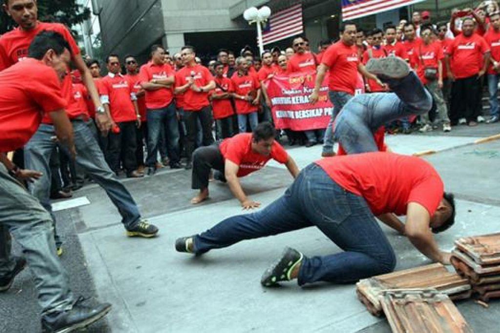 TUNJUK KEKUATAN: Kumpulan Baju Merah anti-Bersih menunjukkan kekuatan dengan pelbagai aksi lasak termasuk memukul kepala dan badan dengan kayu selain aksi memecahkan atap genting dengan kepala. - Foto MALAYSIA KINI